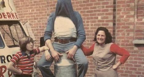 man zit op tinnen bus melk met zoon en vrouw naast zich